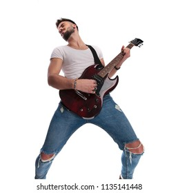 excited young guitarist playing the guitar  and leaning back while standing on white background