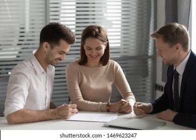 Excited young husband and wife sign contract with realtor renting first shared house together, overjoyed millennial couple put signature on document make deal with broker or banker in office