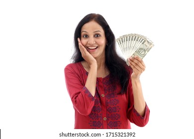 Excited young Indian woman holding currency against white background
