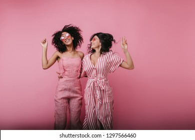 Excited young ladies jumping on pink background and laughing. Studio portrait of african girl with short hairstyle dancing with her best friend