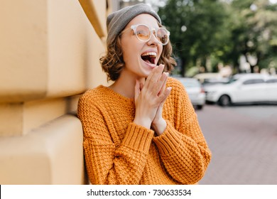 Excited young lady in gray hat laughing on the street beside building. Outdoor portrait of blissful female model in trendy knitted sweater posing with mouth open and looking up on blur background.