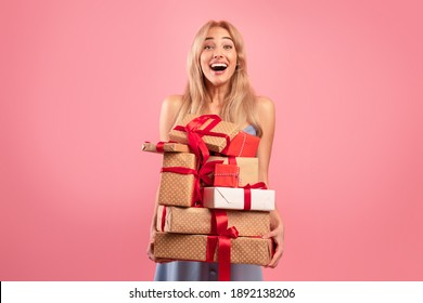 Excited young lady holding stack of holiday gifts on pink studio background. Cheerful millennial woman with pile of festive presents. Birthday, Woman's Day, Valentine celebration concept