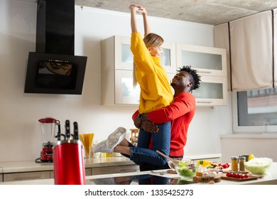 Excited young lady smiling and putting hands up while caring loving boyfriend holding her in his arms in the kitchen