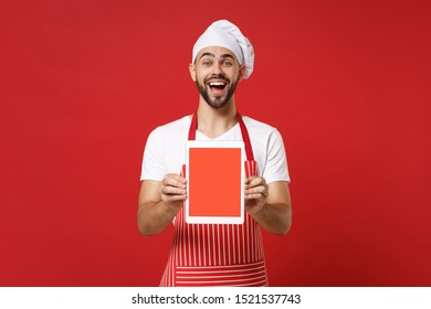 Excited young male chef cook or baker man in striped apron toque chefs hat isolated on red background. Cooking food concept. Mock up copy space. Holding tablet pc computer with blank empty screen