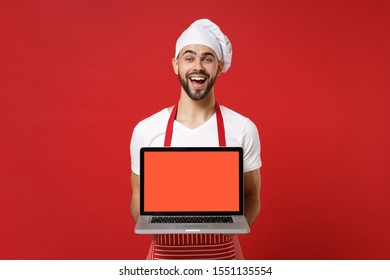 Excited young male chef cook or baker man in striped apron t-shirt toque chefs hat isolated on red background. Cooking food concept. Mock up copy space. Hold laptop computer with blank empty screen