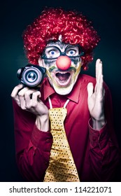 Excited Young Male Photographer Clown Holding Camera While Shouting Out Cheese At A Kids Birthday Party Celebration On Dark Studio Background