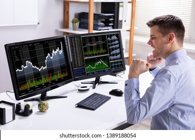 Excited Young Male Stock Market Broker Looking At Graph On Computer At Workplace