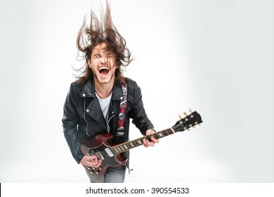 Excited young man in black leather jacket with electric guitar shouting and shaking head over white background