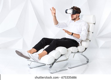 Excited young man is getting experience using VR-headset glasses of virtual reality gesticulating with his hands