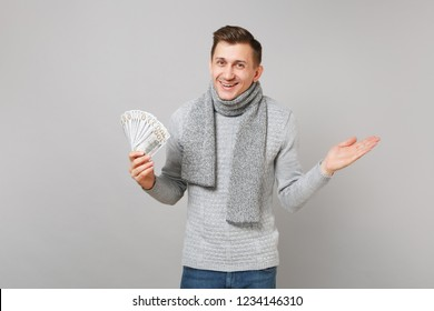 Excited young man in gray sweater, scarf hold lots bunch of dollars banknotes cash money pointing hand aside isolated on grey background. Healthy lifestyle people sincere emotions cold season concept