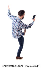Excited young man holding mobile phone reading message on blank screen falling backwards. Rear view. Full body isolate on white background.