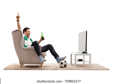 Excited young man with a scarf and a bottle of beer watching football on television and pointing up isolated on white background