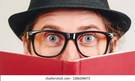 Excited young nerd guy holding book. Nerd in glasses. Funny man looking to camera. Never too late to study. Amazing man has great idea. Male nerd hiding behind books. Nerd hipster guy in hat