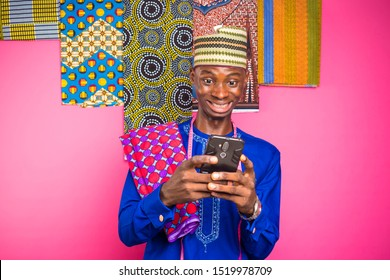 excited young nigerian man viewing something on his mobile phone