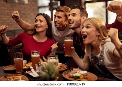 Excited young people watching sports match on TV while drinking beer and eating in a pub.