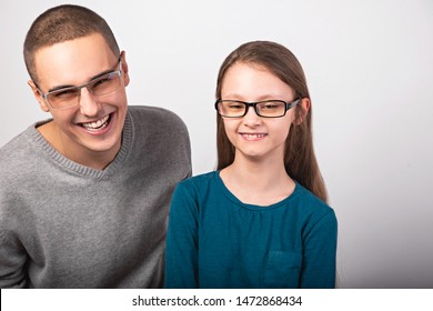 Excited young positive father and toothy lauging kid in fashion glasses hugging on empty copy space background. Closeup portrait
