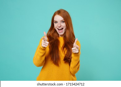 Excited young redhead woman girl in yellow sweater posing isolated on blue turquoise wall background studio portrait. People lifestyle concept. Mock up copy space. Pointing index fingers on camera