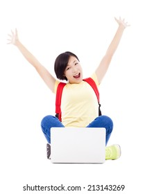 excited young student girl sitting with a laptop and raising arms