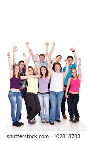 Excited young students with hands raised standing on white background