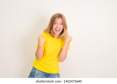 Excited young teenager girl standing isolated over white background make winner gesture. People, teen, emotions, expressions, success, lesure concept.