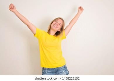 Excited young teenager girl standing isolated over white background with hands up. People, teen, emotions, expressions, success, lesure concept.