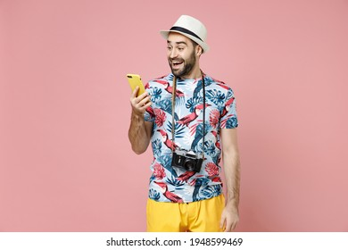 Excited young traveler tourist man in summer clothes, hat using mobile cell phone typing sms message isolated on pink background. Passenger traveling abroad on weekends. Air flight journey concept - Shutterstock ID 1948599469