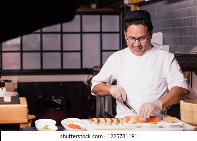 excited young unexperiened chef learning to cut sushi at work. close up photo. copy space. first working day. studing concept