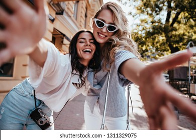 Excited young woman with camera spending weekend with friend. Outdoor shot of spectacular blonde girl making selfie in warm day.