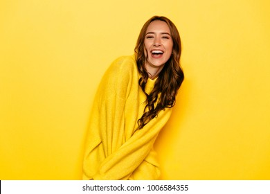 Excited young woman with curly hair in yellow sweater, widely smiling, looking at camera. Isolated on yellow background.