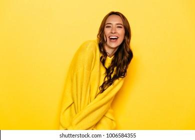 Aufgeregt junge Frau mit lockigen Haaren in gelbem Pullover, weithin lächeln, Blick auf die Kamera. Einzeln auf gelbem Hintergrund.