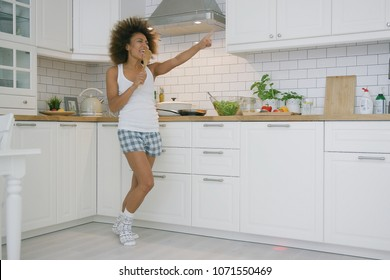 Excited young woman dancing expressively and singing with spoon while cooking meal in morning time in kitchen at home.