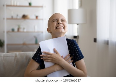 Excited young woman fighting against oncology scream in delight clasp document with good test result to chest. Happy sick lady laugh thank god hold paper letter medical conclusion that cancer receded.