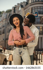 Excited young woman laughing while standing in the street with boyfriend. His hands on her belly