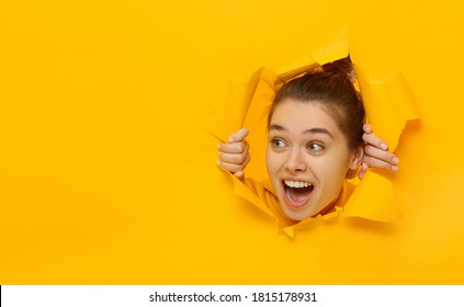 Excited young woman looking through hole in paper at left with eyes round with surprise, isolated on yellow background with copy space