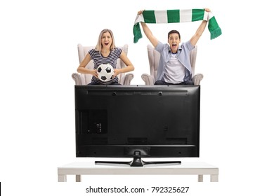 Excited young woman and a young man seated in armchairs watching football on television isolated on white background