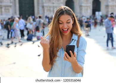 Excited young woman receiving good news on line in a smart phone outside on the street