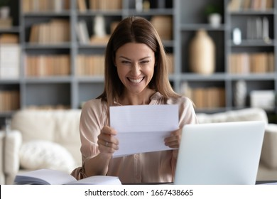 Excited young woman sitting at workplace at home, holding paper letter, received bank loan approval notice, job promotion. Happy businesswoman getting good news notification, money refund document.