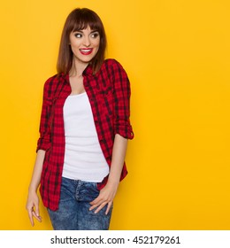 Excited young woman in unbuttoned red lumberjack shirt and jeans looking away. Three quarter length studio shot on yellow background.