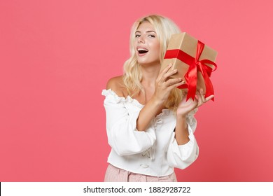Excited young woman in white casual clothes hold red present box with gift ribbon bow isolated on bright pink colour background, studio portrait. Valentine's Day Women's Day birthday holiday concept