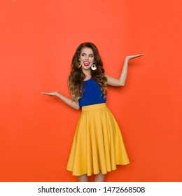 Excited young woman in yellow skirt and blue top is holding hands raised, comparing, looking away and talking. Three quarter length studio shot on orange background.