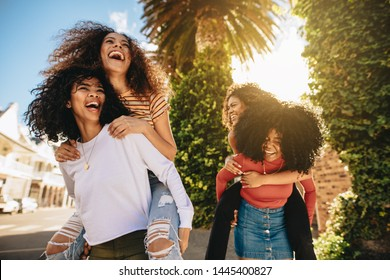 Excited young women enjoying themselves outdoors. Group of female friends piggybacking and having great time in the city.