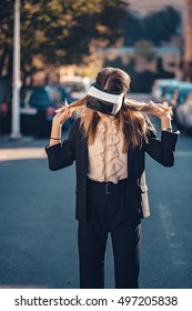 Excited young women using virtual reality headset VR glasses on the street and she is feeling curious in augmented reality with beautiful autumn morning sunrise light in her amazing long hair