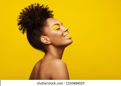 Excitement African American Fashion Model profile portrait . Satisfied Brunette young woman with afro hair style,creative yellow make up, lips and eyeshadows on colorful background