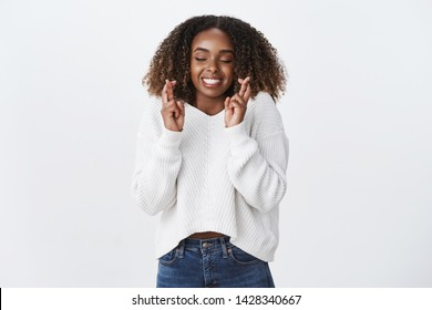 Excitement, anticipation surprise concept. Charming smiling happy african-american young woman cross fingers good luck closed eyes smiling gladly make wish dream party went well, white background