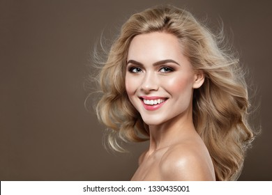 Excitement Blonde haired Woman Portrait with blue eyes and Healthy Long Shiny Wavy hairstyle. Volume shampoo. Blond Curly permed Hair and bright makeup.