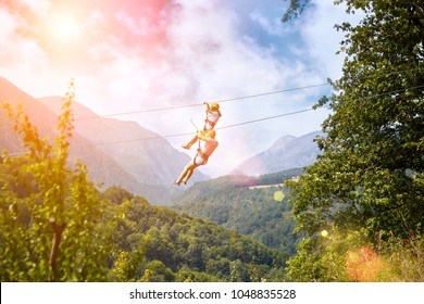 Exciting adventure activity in mountains. Man and woman hanging on a rope-way. Tourists ride on the Zipline through the canyon on blue sky background. Couple in helmets is riding on a cable car