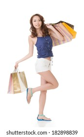 Exciting Asian shopping woman holding bags, full length portrait isolated on white.