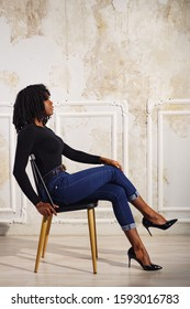 exciting black lady in dark clothes sits cross-legged on wooden chair in room with beige floor walls side view