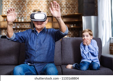 Exciting experience. Cheerful aged man wearing VR glasses while resting with his granddaughter