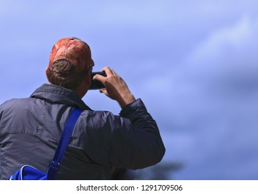 Exciting father at a primary school atlethic meeting in Hartenbos (South Africa) ready to photograph his son in the 50 meter race